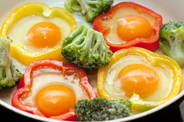 В каждое кольцо аккуратно вылейте по одному яйцу. Посолите и готовьте на небольшом огне, пока яичница не будет готова. Кстати, в просветах между перцем можно приготовить другие овощи или поджарить бекон.