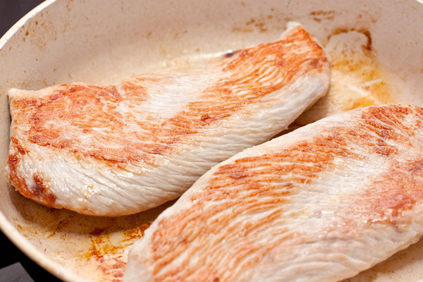 Филе грудки индейки, нарезанное пластинами толщиной 2-3 см обжарьте на большом огне до румяной корочки и доведите до готовности. Не передерживайте мясо, его очень легко пересушить! Оно должно потерять розовый цвет на срезе, но сохранить сочность.