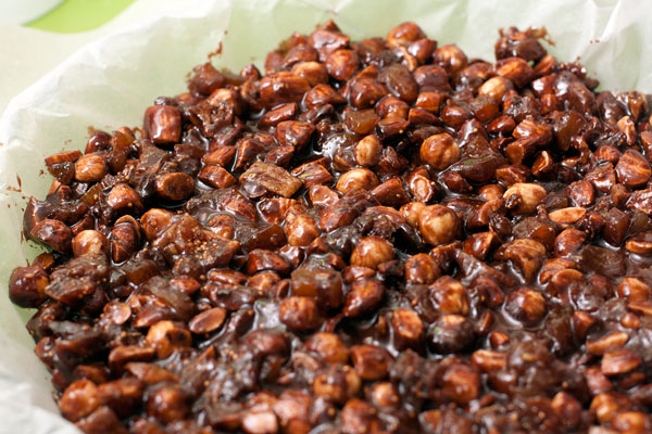 Низкую форму для выпечки застелите пекарской бумагой и слегка смажьте ее маслом. Выложите тесто и разровняйте влажной ложкой.
