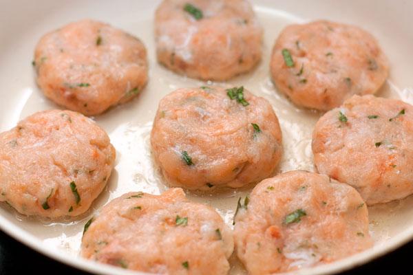 Влажными руками формируйте круглые котлетки толщиной 1-1,5 см и выкладывайте на разогретую сковороду с небольшим количеством масла. Если у вашей сковороды хорошее антипригарное покрытие, то можно готовить вообще без масла, так в красной рыбе содержится много жира, часть которого вытопится во время обжаривания.