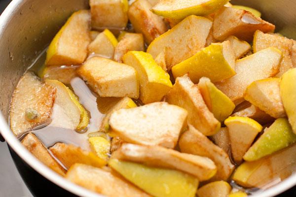 За сутки айва выделит достаточно сока, чтобы растворить сахар. Поставьте кастрюлю на небольшой огонь и варите при слабом кипении без крышки, периодически помешивая.
