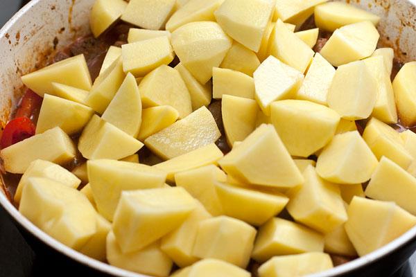 Пока тушится мясо, очистите и нарежьте картофель также, как баранину. Положите его в сковороду, перемешайте. накройте крышкой и тушите еще полчаса до мягкости.