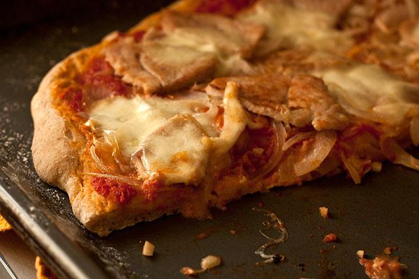 Поставьте пиццу в духовку и выпекайте 12 минут, пока края не станут золотистыми.