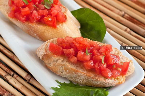 Помидоры разложите поверх хлеба, сверху немного посолите. Можно посыпать измельченной петрушкой и черным перцем.