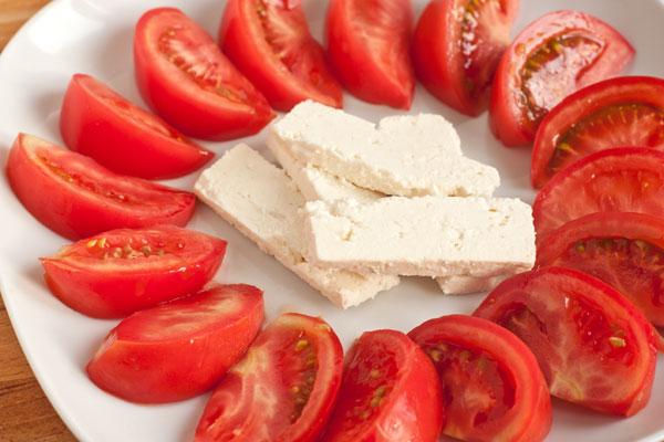 На широкой тарелке разложите дольки помидоров по кругу, в середину положите кусочки брынзы.