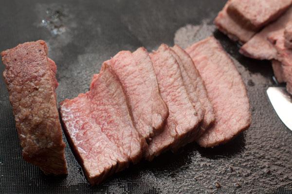 Готовую говядину нарежьте поперек волокон тонкими ломтиками.
