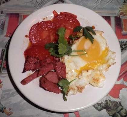 Помидоры обжарить на сливочном масле и выложить к колбасе на тарелку. Яйца пожарить на сковороде и выложить на тарелку. Посыпать свежей зеленью