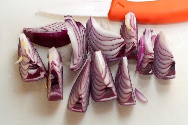Очищенный красный лук разрежьте вдоль на 8-12 долек.