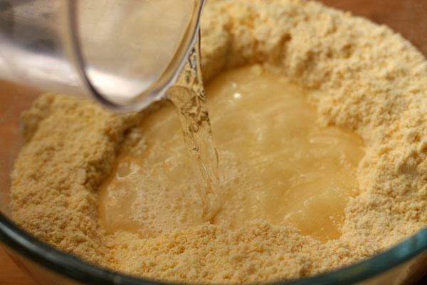Оба вида муки просейте в широкую миску, добавьте соль и нарезанное кубиками масло и тщательно измельчите все вместе до состояния мелкой крошки. Влейте в углубление в середине 200 мл теплой воды.