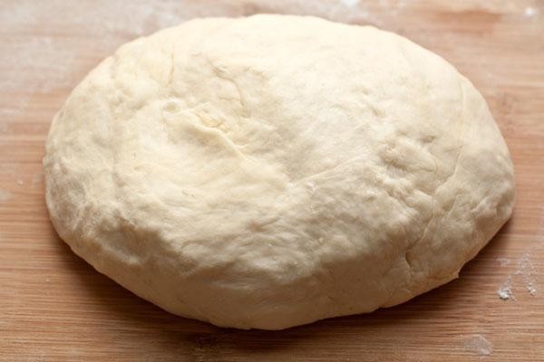 Добавьте 220 мл горячей (около 60 градусов) воды, замесите мягкое и пластичное тесто. Месите хорошо, пока тесто не будет хорошо отставать от рук. При необходимости можно подсыпать чуть-чуть муки.