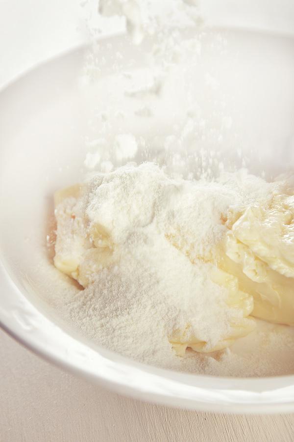 Смешиваем чуть подтаявшее сливочное масло с сахарной пудрой, сухим молоком.
