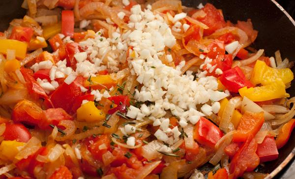 В сковороде, где жарилась курица, спассеруйте лук до прозрачности, затем положите помидоры и перец. Готовьте 5 минут на сильном огне, помешивая. Ближе к концу добавьте мелко измельченный чеснок и листья розмарина.