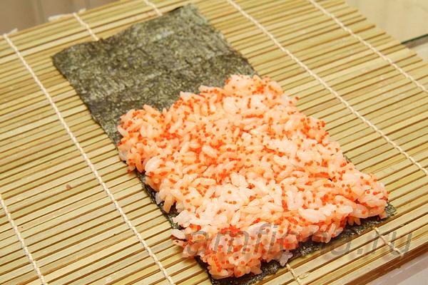 Возьмите пару столовых ложек икры тобико любого цвета и перемешайте с рисом для суши. Лист нори разделите пополам поперёк перфорации на листе. Смочив водой руки, выложите окрашенный рис на водоросли ровным слоем.
