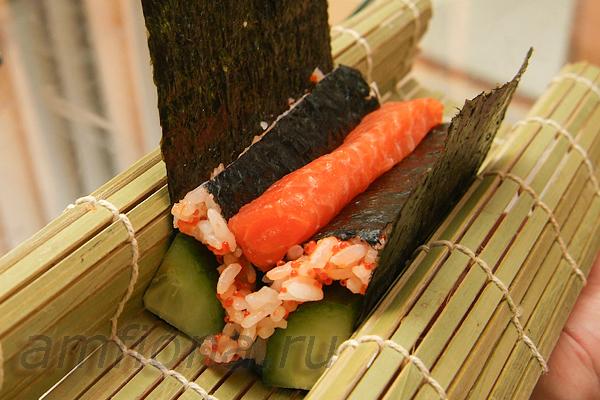 В середину положите начинку. Можно взять любые овощи, японский омлет и т.д. В данном случае использовано небольшое количество лосося для суши.