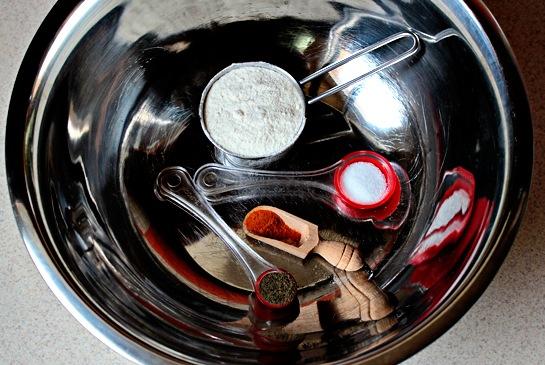 Подогрейте духовку до 200 C. В большой миске смешайте ¼ кружки муки, ½ чайную ложку соли, ¼ чайной ложки черного и ¼ чайной ложки красного перца.