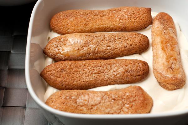Печенье савоярди быстро окунайте холодный в кофе с двух сторон и выкладывайте в форму на крем.