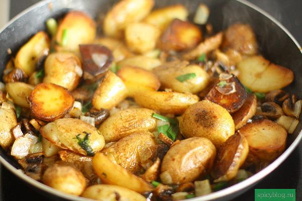 Пока курица запекается, приготовьте простой гарнир. Помойте картофель и разрежьте картофелины пополам, самые большие на 4 части. Отварите их в кипящей подсоленной воде 10-15 минут. Разогрейте сковородку на сильном огне, влейте пару столовых ложек масла. Введите картофель. Обжаривайте 5 минут, но не слишком часто переворачивайте, нам нужна корочка. Затем добавьте лук, чеснок и крупно нарезанные грибы. Посолите и обильно поперчите. Обжаривайте еще 5-7 минут, затем снимите с огня и добавьте мелко нарубленный зеленый лук.