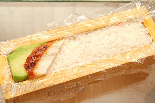 Подготовьте несколько небольших кусочков угря для суши, лосося и авокадо. Выложите их на рис вплотную друг к другу.