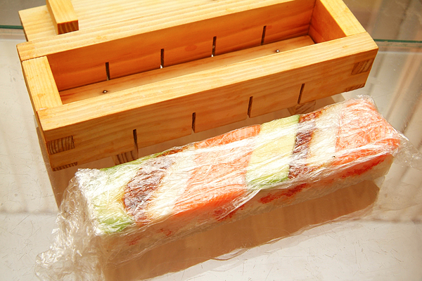 еще раз слегка придавите суши прессом и достаньте из ящичка.