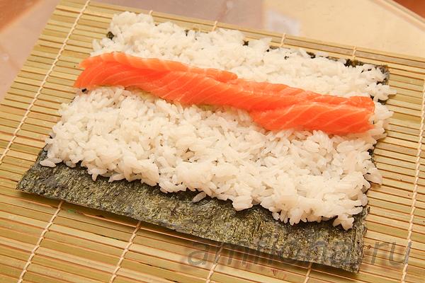 Нанесите немного пасты васаби на рис и выложите несколько ломтиков сёмги для суши.