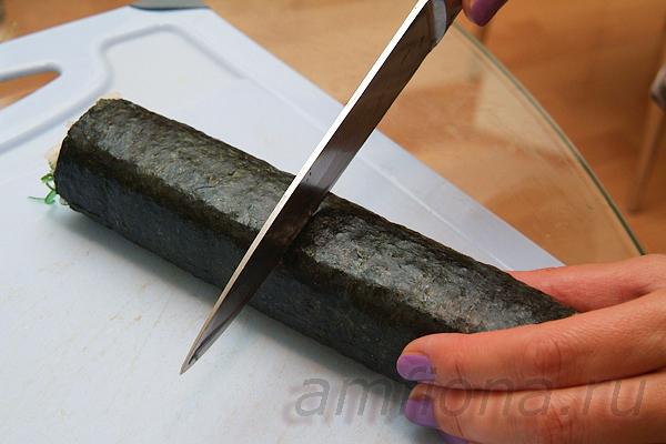 Перенесите ролл на разделочную доску, смочите лезвие ножа и разрежьте ролл на две половинки.