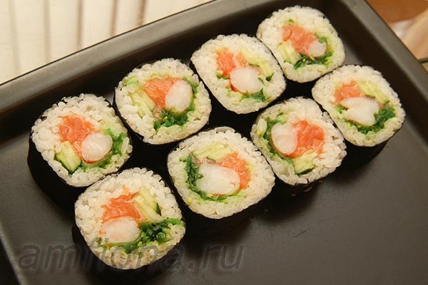 Из оставшихся креветок и рыбы приготовьте еще один толстый ролл. Выложите ролл на тарелку и подайте с соевым соусом, имбирём и васаби.