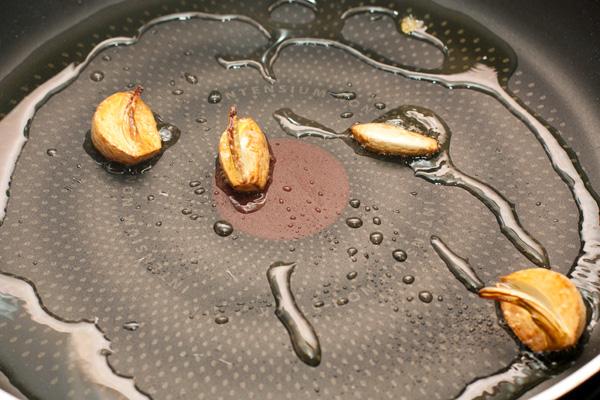 Поставьте варить пасту в большом количестве сильно кипящей подсоленной воды.  Очищенный чеснок раздавите лезвием ножа или разрежьте пополам, бросьте на разогретую сковороду с небольшим количеством оливкового масла. Когда он станет золотисто-коричневым и появится характерный приятный запах, удалите чеснок. Больше он нам не понадобится.