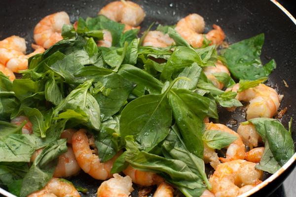 Вымытый и подсушенный базилик крупно нарвите, положите в сковороду к креветкам и перемешайте. Посолите и поперчите по вкусу.