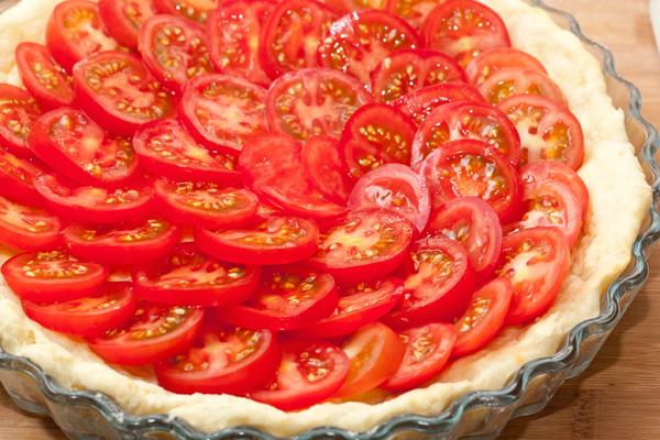 На подготовленную основу выложите ломтики помидоров внахлест, немного посолите.