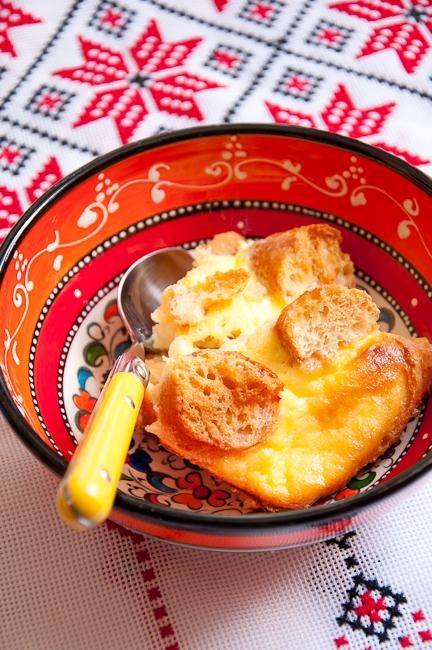 Вылить яично-молочную смесь на хлеб, сверху положить совсем сухие кусочки хлеба, чтобы они стали хрустящими.    Поставить форму с пудингом в форму большего размера и налить немного горячей воды (2 см). Выпекать 45-50 минут при температуре 160 градусов, пока верх не зарумянится.
