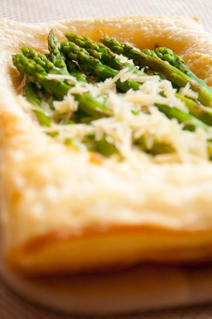 Несколько листов бездрожжевого слоеного теста раскатать до толщины 0,5 см. Несколько столовых ложек сыра маскарпоне смешать с натертым пармезаном и распределить смесь по листу теста, оставляя края свободными.   Выложить спаржу на смесь сыров и выпекать в верхнем отделе духовки при температуре 190 градусов 15 минут. Края перед выпечкой можно смазать яичным белком, тогда выпечка будет  золотистого цвета. Подавать горячим, посыпав пармезаном.