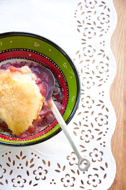 Муку и разрыхлитель смешать, холодное масло втереть в муку, чтобы получилась масса, напоминающая раскрошенное печенье. Добавить сахар (30 граммов), перемешать, влить кефир. Должно получиться густое тесто. Лучше добавлять кефир, йогурт или сыворотку постепенно, чтобы контролировать густоту теста, оно должно быть как очень густая сметана.  Выложить крыжовник в огнеупорную форму, сверху ложкой выложить тесто, посыпать сахаром (20 граммов) и поставить запекаться в духовку с температурой 190 градусов на 20-25 минут, или пока тесто не станет золотистого цвета.    Подавать теплым.