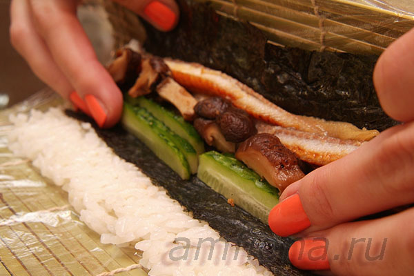 затем начните сворачивать ролл, приподняв бамбуковый коврик за край и придерживая начинку пальцами.