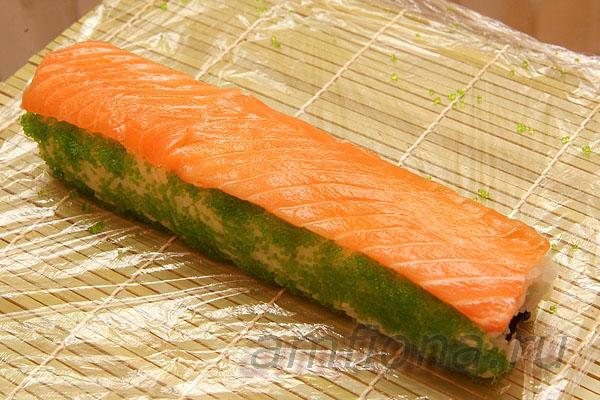 Положите на ролл несколько ломтиков лосося для суши и прижмите их ковриком.