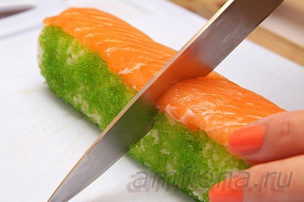 Ролл готов к нарезке! Возьмите острый нож, смочите лезвие водой и разрежьте ролл пополам. Затем каждую половину - на три или четыре кусочка. Обязательно протирайте лезвие ножа перед каждым разрезом. Если икра прилипает к пальцам, возможно, вам будет проще резать ролл, накрыв его пищевой плёнкой.