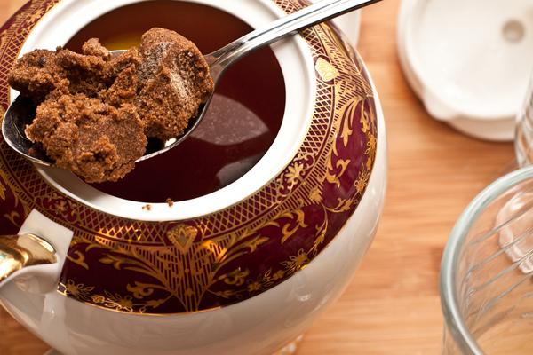 Выжмите в чай лимон, добавьте специи и коричневый сахар. Размешайте, чтобы сахар растворился. Дайте настояться под крышкой 5 минут.