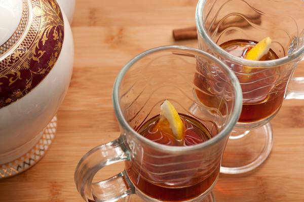 В стаканы налейте ром, положите по кусочку лимона и налейте процеженный чай.