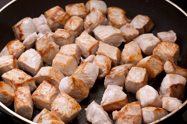 На большом огне обжарьте свинину со всех до золотисто-коричневой корочки.