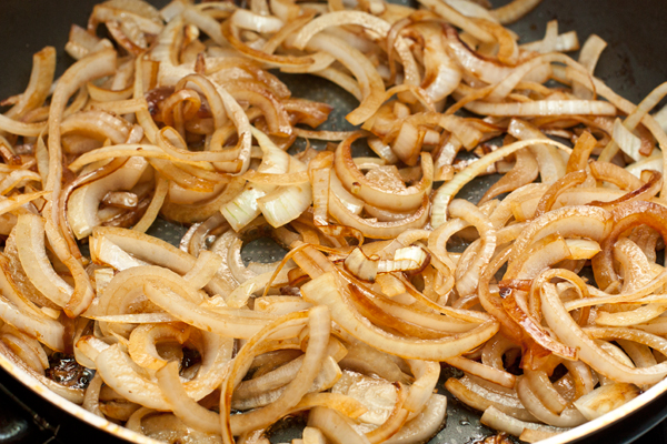 На той же сковороде, убавив огонь, слегка обжарьте лук, нарезанный тонкими полукольцами.