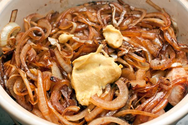 В толстостенную кастрюлю выложите мясо, сверху лук добавьте горчицу, соль и специи.
