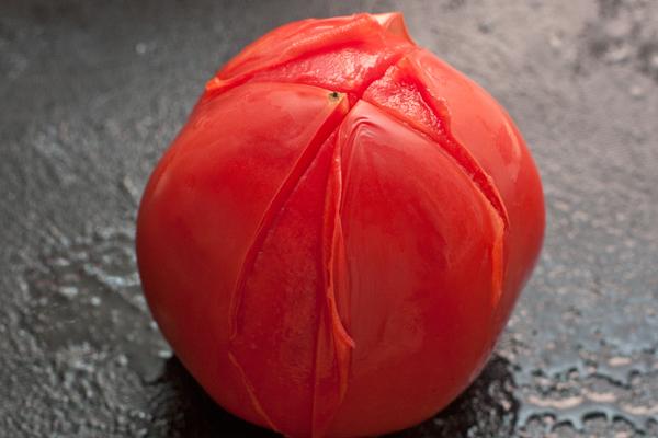 На помидоре сделайте снизу неглубокий крестообразный надрез, опустите на полминуты в кипяток, затем снимите кожицу.