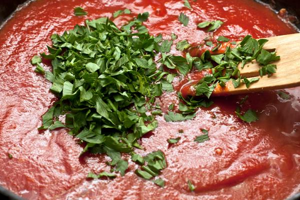 Затем добавьте томатное пюре и измельченные листья петрушки. Если хотите более итальянский акцент, вместо петрушки добавьте базилик.  Доведите соус до кипения и готовьте на небольшом огне, помешивая 3-4 минуты.