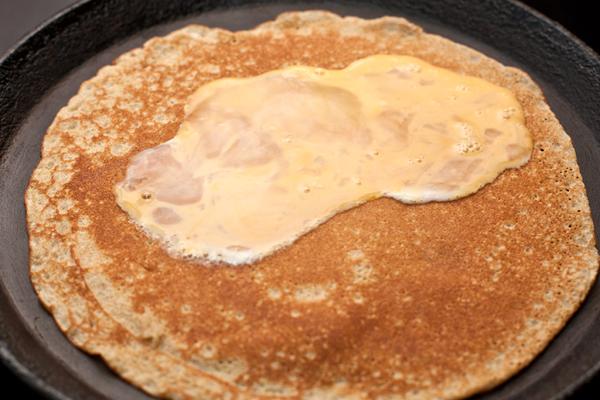 Как только блин поджарится с одной стороны, переверните и сразу же налейте на поджаренную сторону 2-3 ст.л. яйца. Когда оно начнет схватываться, сложите блин пополам и обжарьте с двух сторон.