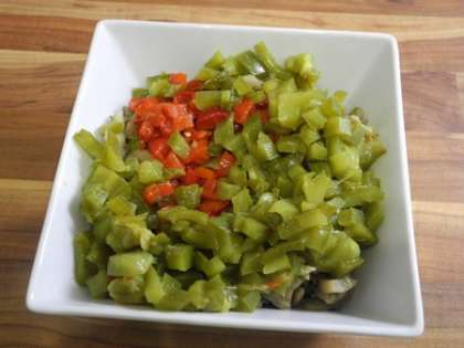 С перцев снять кожицу, мякоть мелко порезать и сложить в салатницу к баклажанам