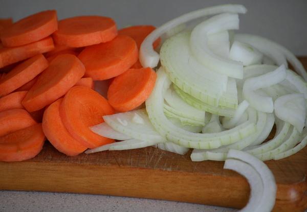 В это время очищаем лук с морковью и нарезаем, лук полукольцами, а морковку кружочками или полукружками: