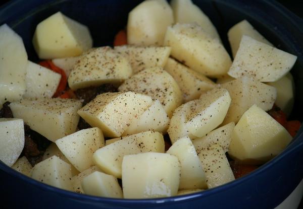 Через 40 минут достаем форму из духовки, добавляем картофель, солим, перчим по вкусу и осторожно перемешиваем: