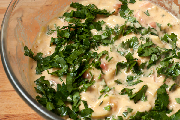 В тесто добавьте нарезанные овощи и зелень. Перемешайте.