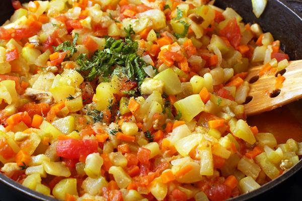 За 2-3 минуты до окончания приготовления добавьте мелко нарезанный чеснок и зелень. Если вы будете консервировать икру из кабачков на зиму, то добавьте по 1-2 чайной ложке уксуса на каждый килограмм кабачков.