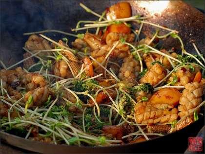 Для стирфрая очень важно заранее приготовить все ингредиенты, чтобы во время жарки ни на что не отвлекаться: имбирь, чеснок и острый перец мелко порубил; мини-початки кукурузы нарезал поперек на три части, а болгарский перец, освободив от семян и перепонок, на небольшие квадраты; брокколи разобрал на соцветия, а у грибов еноки отрезал корневую часть – она несъедобна; у проростков гороха (подойдут и проростки сои) отрезал лишнюю часть стеблей; сычуаньский перец обжарил на сухой сковороде и растер в ступке; смешал один к одному крахмал и воду.