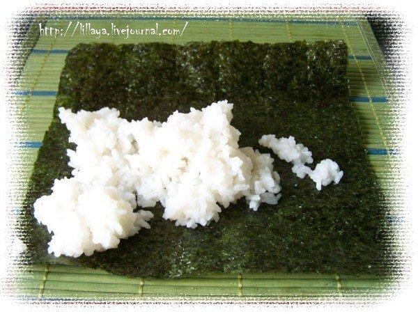 Надо взять бамбуковый коврик, с его помощью мы будем катать суши. И мисочку с водой и рисовым уксусом. В нее надо макать пальцы, чтобы рис не прилипал.  На коврик кладем лист нори (сушенные прессованные водоросли) и рис.